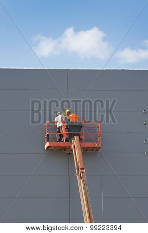 Workers In Lifting Cage