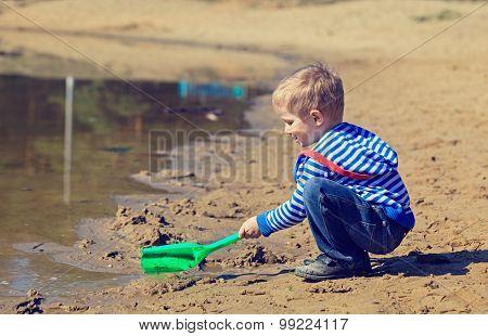 little boy digging sand in spring