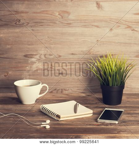 Working table with notepad, coffee cup , pen , smartphone , headphone, plant pot. Wooden table background with copy space on top. Instant photo vintage split toning color effect.