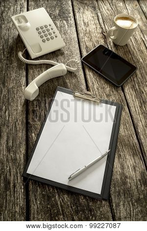 Telephone, Tablet, Coffee And Paper On Table