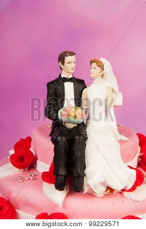 Pink wedding cake with red roses and vintage couple on top