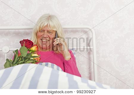 Happy Woman In Bed With Roses And Telephone