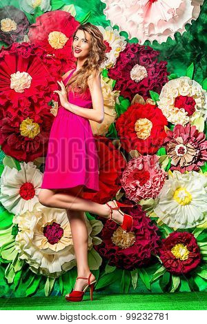 Full length portrait of a beautiful happy young woman posing on a background of bright large flowers. Beauty, fashion. Summer inspiration.