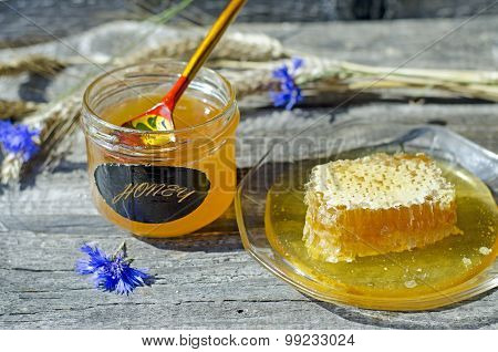 Honey in honeycomb on the glass plate with ears and cornflowers on the wood background, selective fo