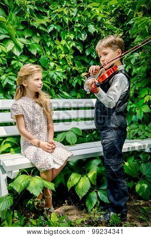 Romantic young violinist playing the violin for pretty little girl at a park. Retro style.