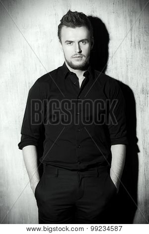 Black-and-white portrait of a fashionable man in black shirt posing at studio. Men's beauty, fashion.