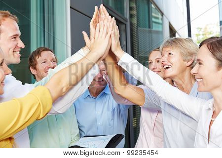 Cheering business people giving high five with their hands outside the office