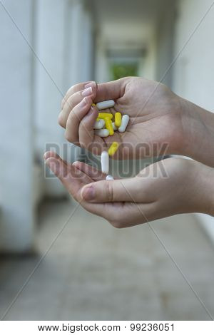 woman pouring a pills from one hand to another