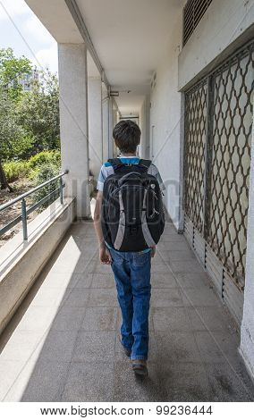 Teenage school boy with a backpack on his back walking to school