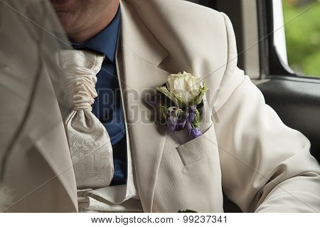 groom's white silk suit with white tie and boutonniere in pocket