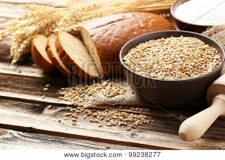 Ears Of Wheat And Bowl Of Flour And Wheat Grains On Brown Wooden Background