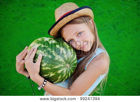 Teen Girl In A Straw Hat Holding A Large Watermelon. Girl Teenager Smiling On A Green Background