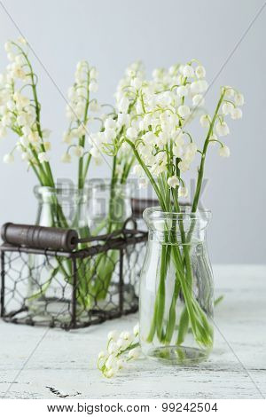 Lily Of The Valley In Bottles On White Wooden Background