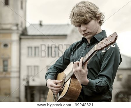 Young man play on the acoustic guitar on the street