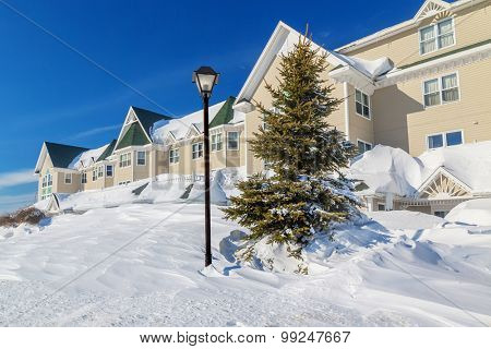 A giant snowbank in front of a north american building.