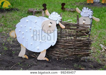 Landscape Design: two sheep on a background of plywood fence of twigs