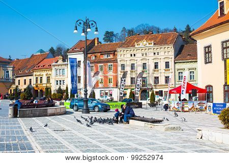 People Feeding The Pigeons At Council Square In Downtown Of Brasov, Romania.