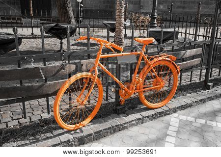 Vibrant orange bicycle on the gray background