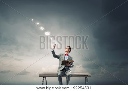 Young businessman sitting on bench with book in one hand and mobile phone in other