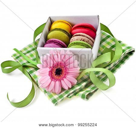 Colorful macaroons in a paper box with holiday ribbon isolation on a white background