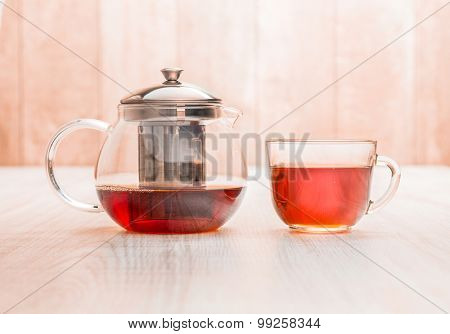 Teapot and cup of tea on wood table background.