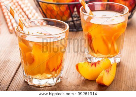 Homemade Ice Tea With Peach Slices In Glasses With Straws