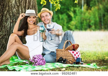 Loving couple with wine relaxing on nature