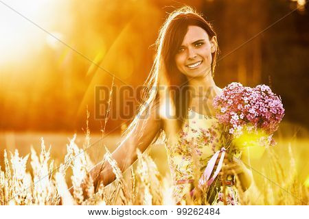 Beautiful girl with flowers on sunny background