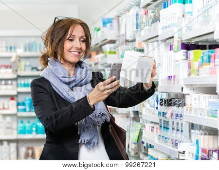 Smiling female customer scanning product through mobile phone in pharmacy