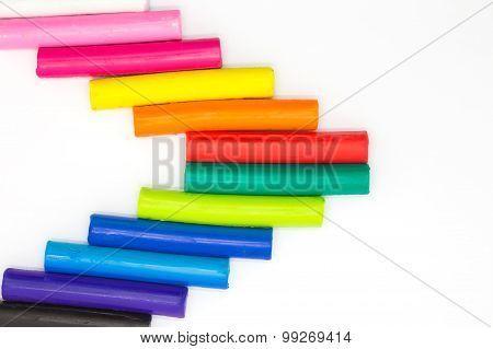 Rainbow colours clay sticks on white background