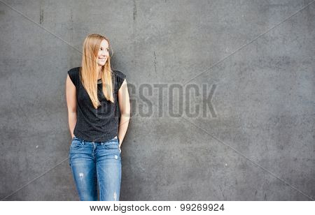 Teenage girl in front of concrete wall looking to the side