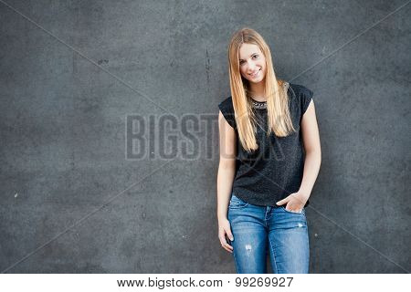 Attractive girl in front of concrete wall