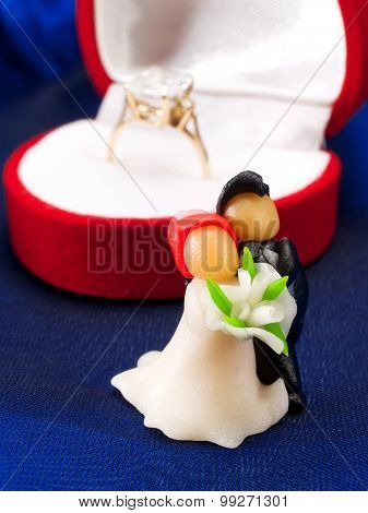 Wedding Cake Figurines And An Engagement Ring