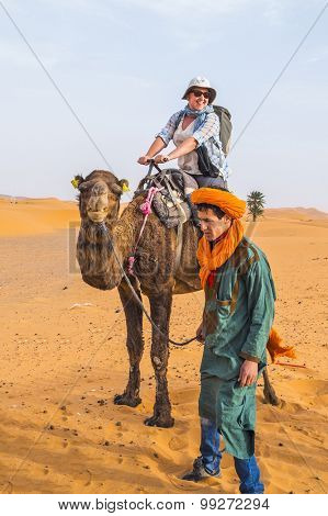 MERZOUGA, MOROCCO, APRIL 13, 2015: Local man in traditional attire helps tourist during a camels ride on sand dunes of Erg Chebbi