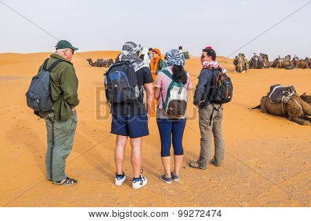 MERZOUGA, MOROCCO, APRIL 13, 2015: Tourists waits for a camel ride on sand dunes of Erg Chebbi