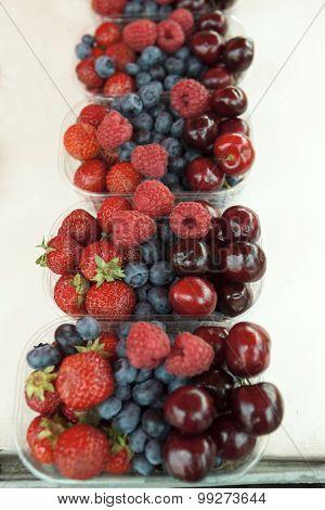 Fresh  raspberries strawberries cherries blueberries in the box on the market.