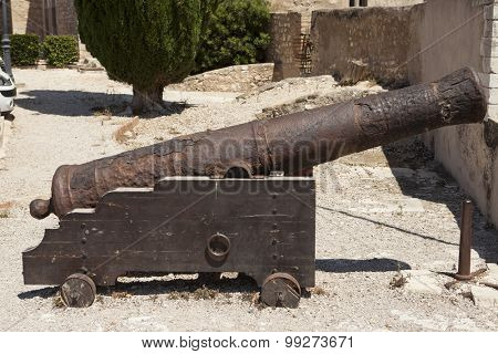 Old cast iron Spanish cannon on a gun carriage to the fortress wall.