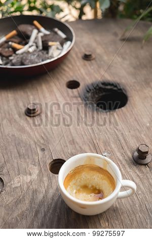 Empty coffee cup after drink with cigarette butt on wood table