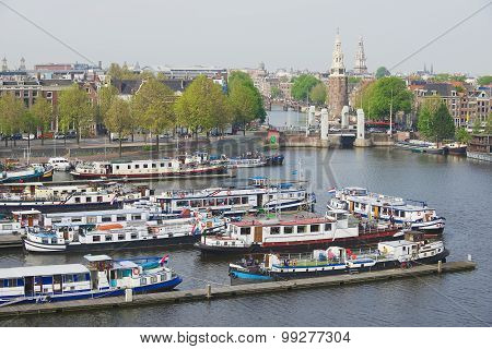 View to the historical building and canal with boats in Amsterdam, Netherlands.