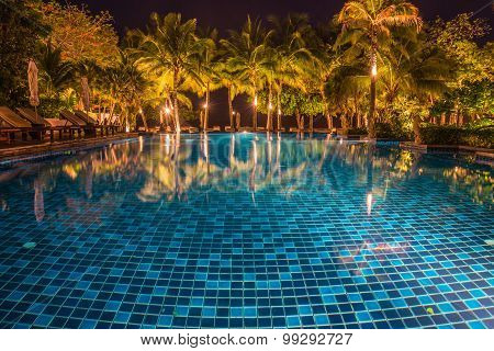 Blue Swimming Pool With Light Reflections At Night