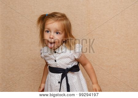 Little Girl Shows Tongue. Emotional Child.