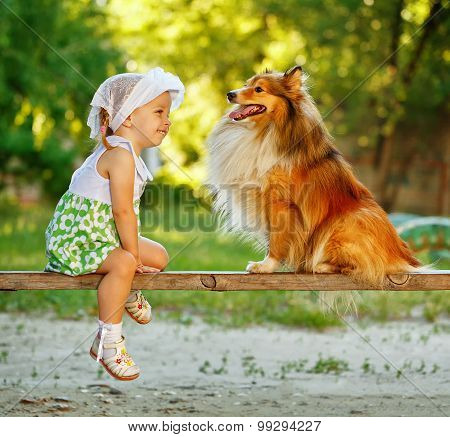 Little Girl And Dog Sitting On A Bench.