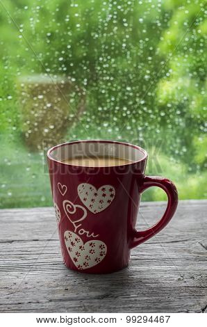 Tea With Milk In The Red Cup Against Window With Rainy Day View