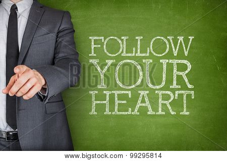 Follow your heart on blackboard with businessman