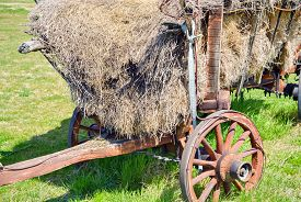 stock photo of wagon  - Closeup of a wooden cargo wagon in the village with haystack - JPG