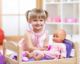picture of baby doll  - cute baby plays in doctor with toy doll and stethoscope  - JPG