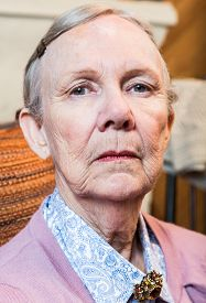 stock photo of matron  - Stern elderly lady in pink sweater looking down at camera - JPG