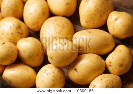 Fresh organic young potatoes on wooden background