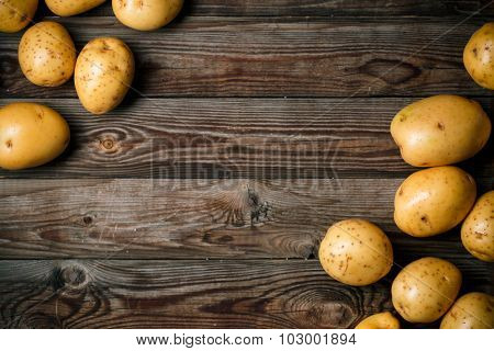 Bunch of potatoes on wooden background close up, space for text