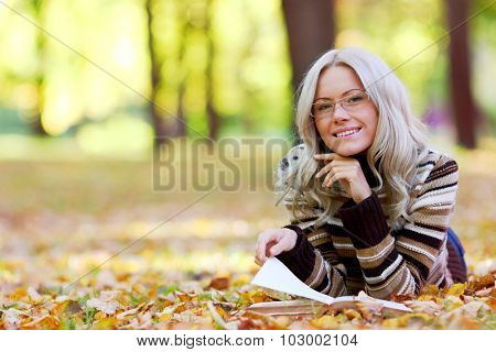 Woman lying on fallen leaves in autumn park and reading a book